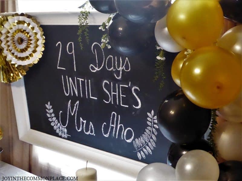 Chalk Board with black & gold balloon garland